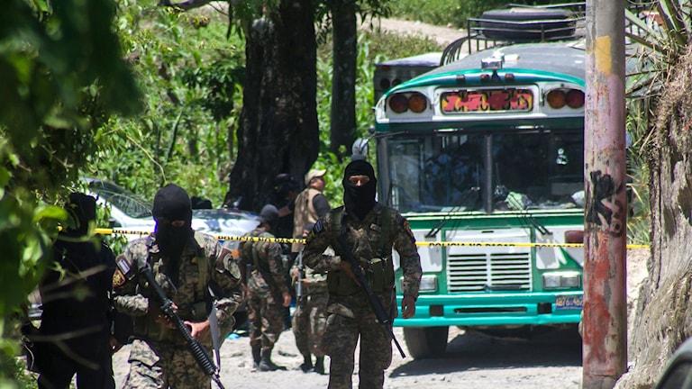 Soldater vaktar platsen efter att en buss blivit attackerad i San Pedro Perulapan, El Salvador, onsdagen den 5 augusti 2015. Beväpnade män ombord på bussen nära  huvudstaden öppnade eld, dödade fyra personer och skadade flera andra. Foto: AP Photo/Salvador Melendez