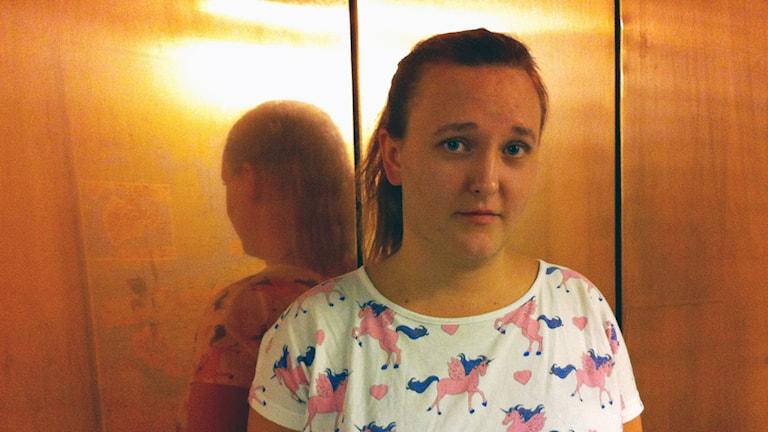 kvinna framför en kopparvägg