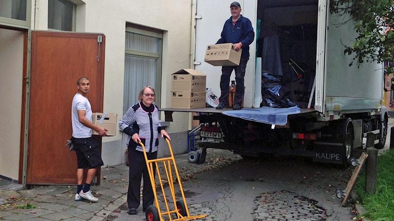 tre personer flyttar lådor in i lastbil