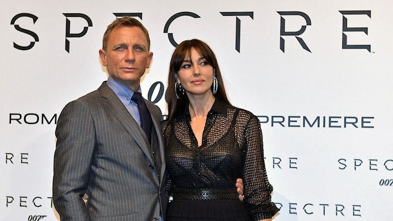"""En man klädd i grå kavaj och en kvinna i svart blus framför text """"Spectre"""". Foto: AFP/Tiziana Fabi"""
