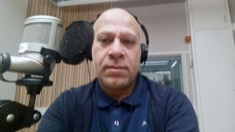 man klädd i blått sitter i radiostudio med en mic i förgrunden och vit vägg och studiofönster i bakkgrunden. Foto: Nazar Akram