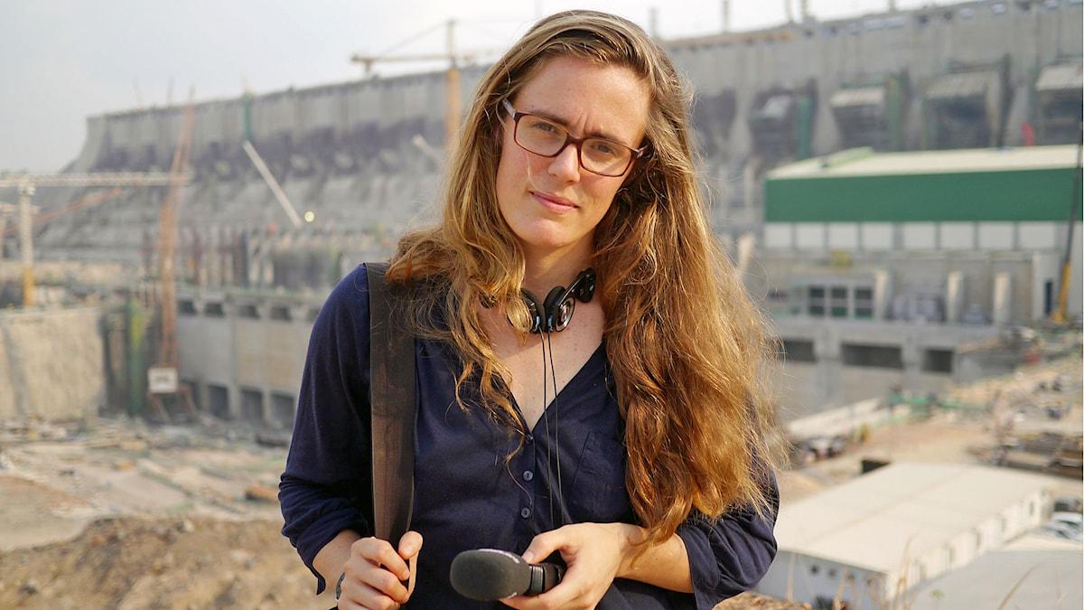 kvinna med glasögon och lågt utsläppt hår, håller microfon och hörlurar runt halsen framför ett vattenkraftverk. Foto: Sveriges Radio