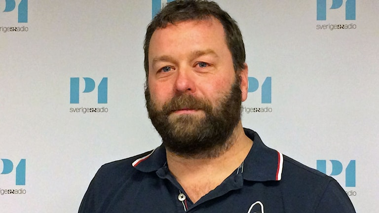 Man i skägg pcj blå piké framför P1-morgons logga. Foto: Sveriges Radio