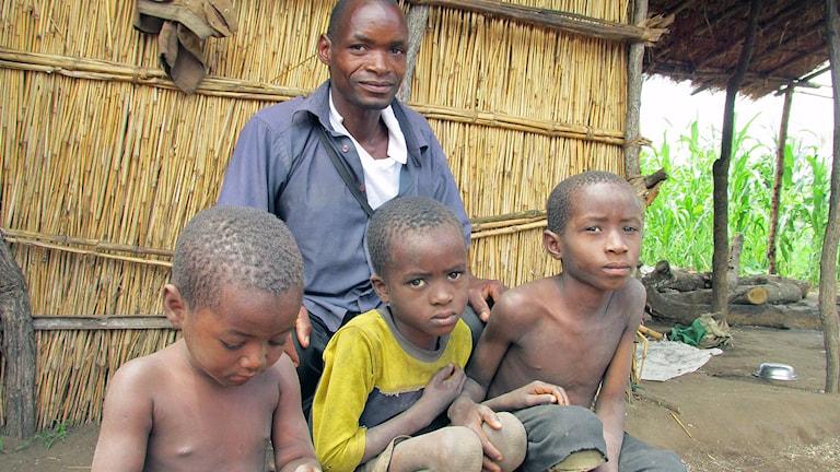 man och tre barn sittandes på marken framför hydda