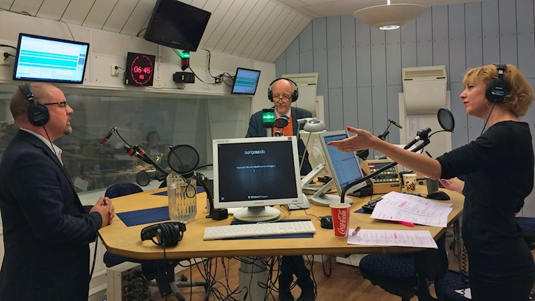 tre personer runt ett studiobord i en radiostudio