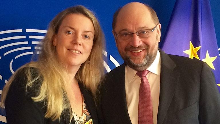 EU-reporter Ci Holmgren, blont långt hår, står till vänster om Martin Schulz, EU-parlamentets talman, man i medelålden, glasögon, kavaj, röd slips.