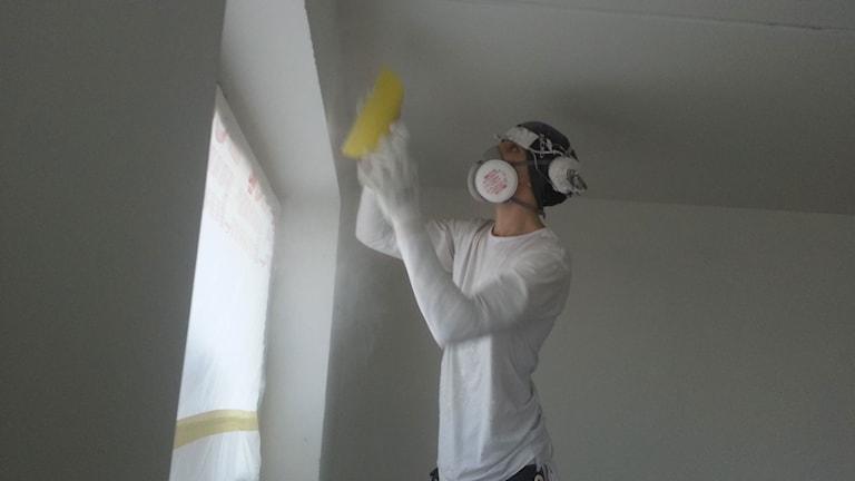 Målare bär muskydd och öronkåpor, håller i en svamp. Vit klädd i ett vitt rum vid och står vid ett fönster