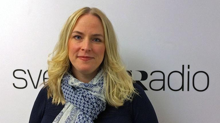 blond kvinna med sjal framför vitsvart sr-logga
