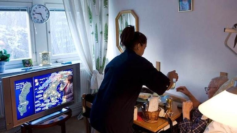 Omsorg på äldreboende - sköterska hjälper äldre person på boende i Stockholm.