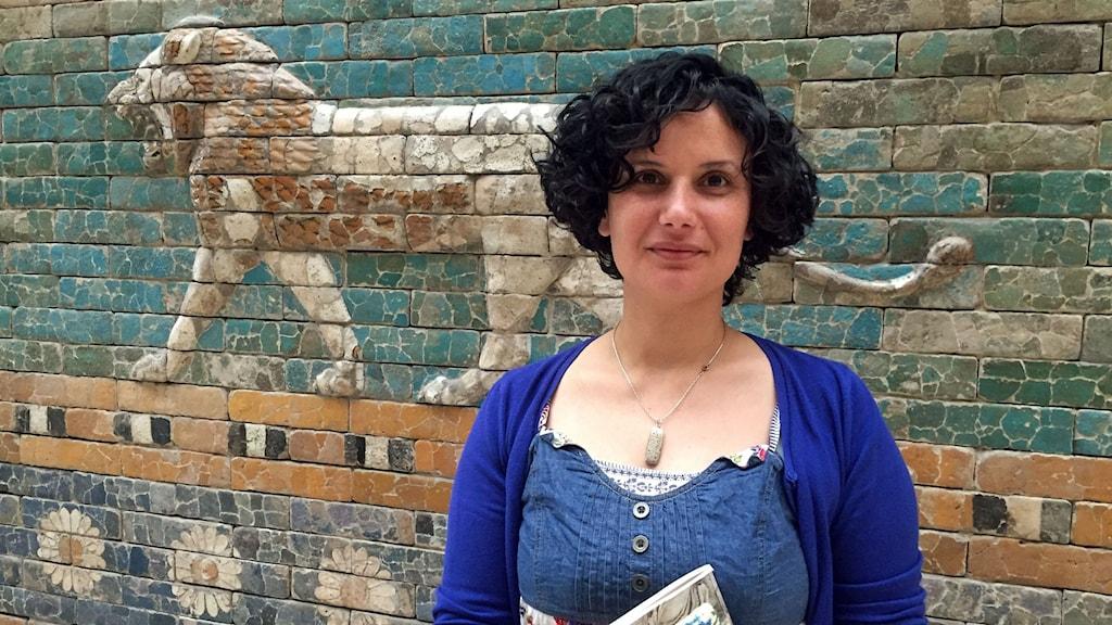 Författaren Kefah Ali Deeb  guidar flyktingar på några av Berlins muséer. Bland kulturarvet från hemtrakterna känner hon sig hemma, samtidigt som hon är ledsen över att varken föremålen eller människorna får vara säkra i hemlandet. Daniela Marquardt/Sveriges Radio