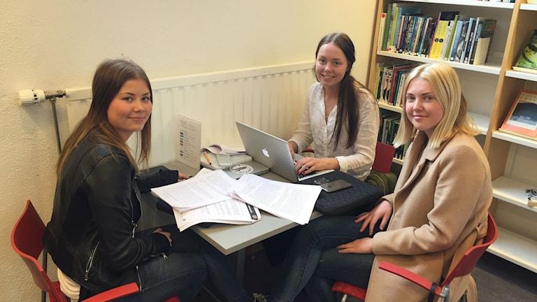 Tre tjejer i 18års åldern som sitter vid ett bord och studerar.