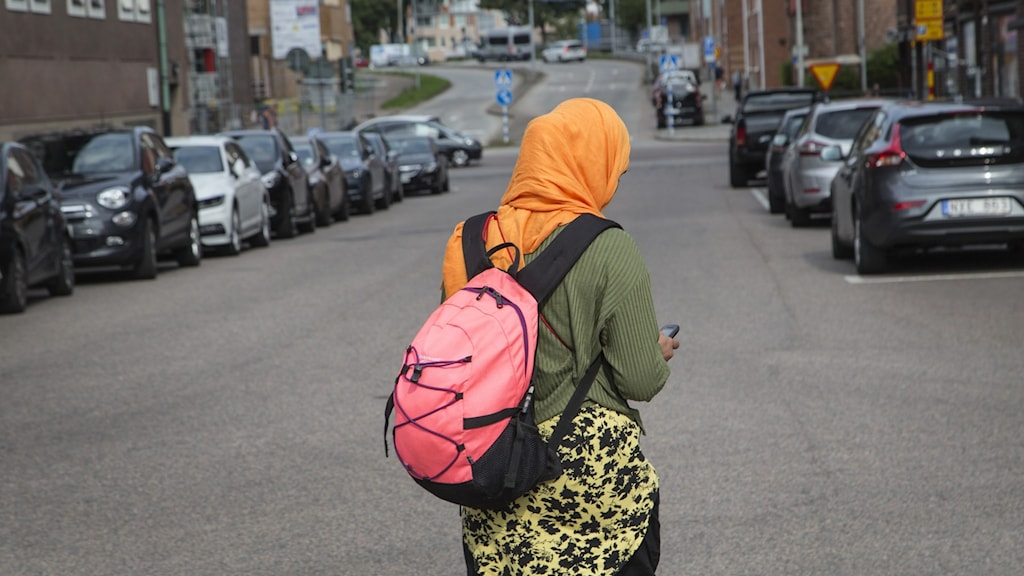 Kvinna med rosa ryggsäck och orangea hijab.