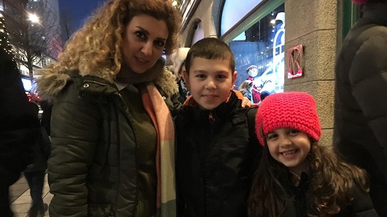 Waad Dagher med barnen Ralph och Celine i vinterkläder på en gata.