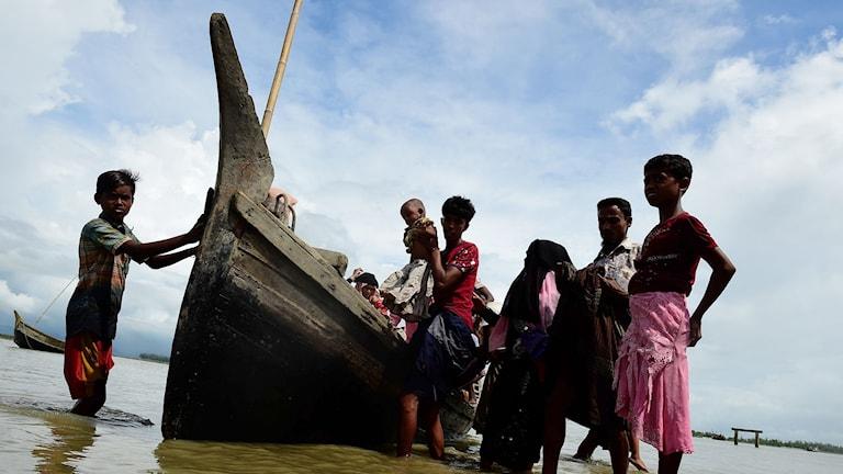 Människor står omkring en träbåt med fötterna i vattnet.