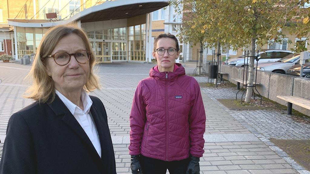 Två kvinnor framför sjukhusentré.