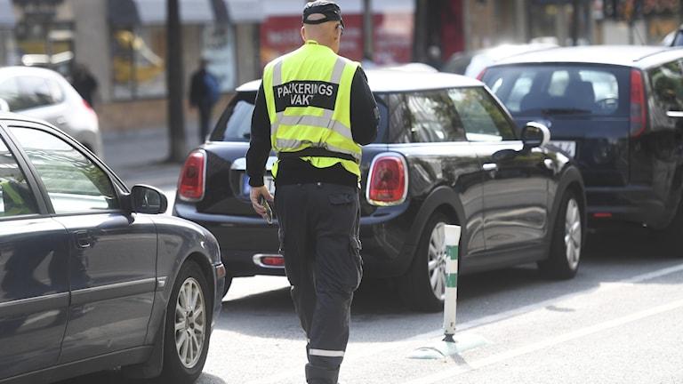 Parkeringsvakt kontrollerar parkerade bilar. Arkivbild.