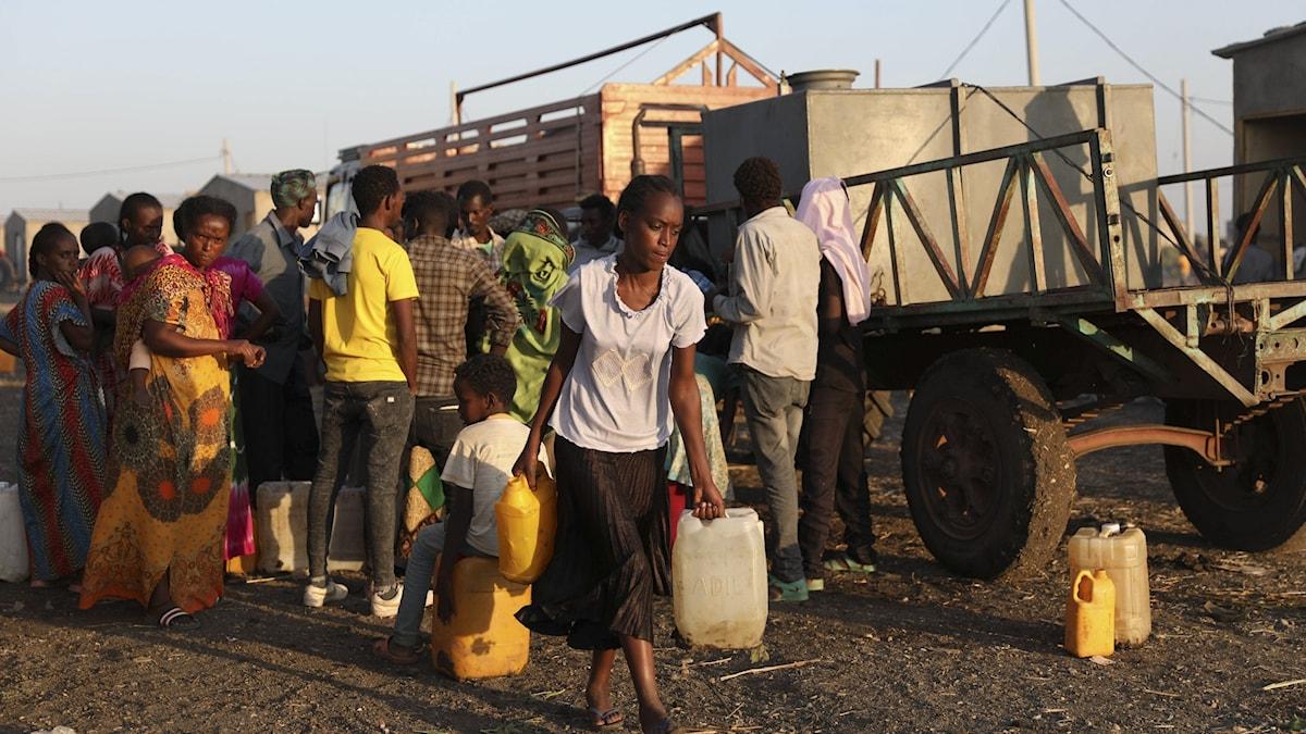 Flyktingar som samlats framför en rad fordon. Där kan man hämta vatten.