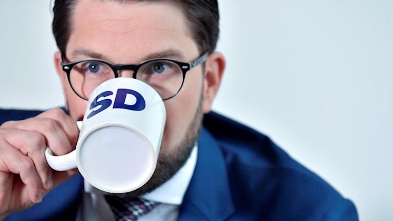 En man dricker ur en kopp.