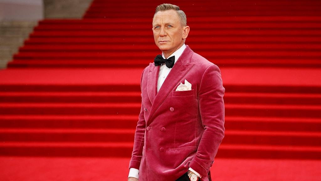 Man i röd sammetskavaj och svarta byxor står på en röd matta.