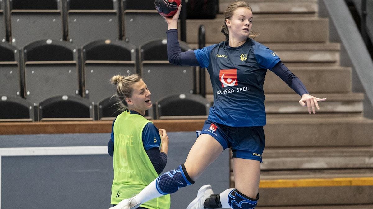 Kvinna högt upp i luften och tar sats för att kasta iväg en handboll.