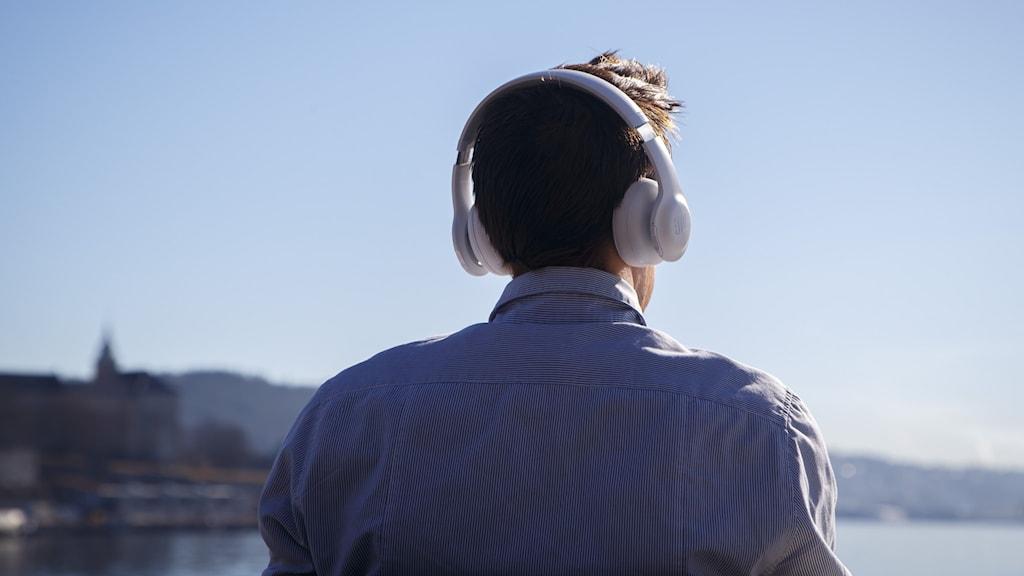 Man med stora hörlurar utomhus sedd bakifrån.