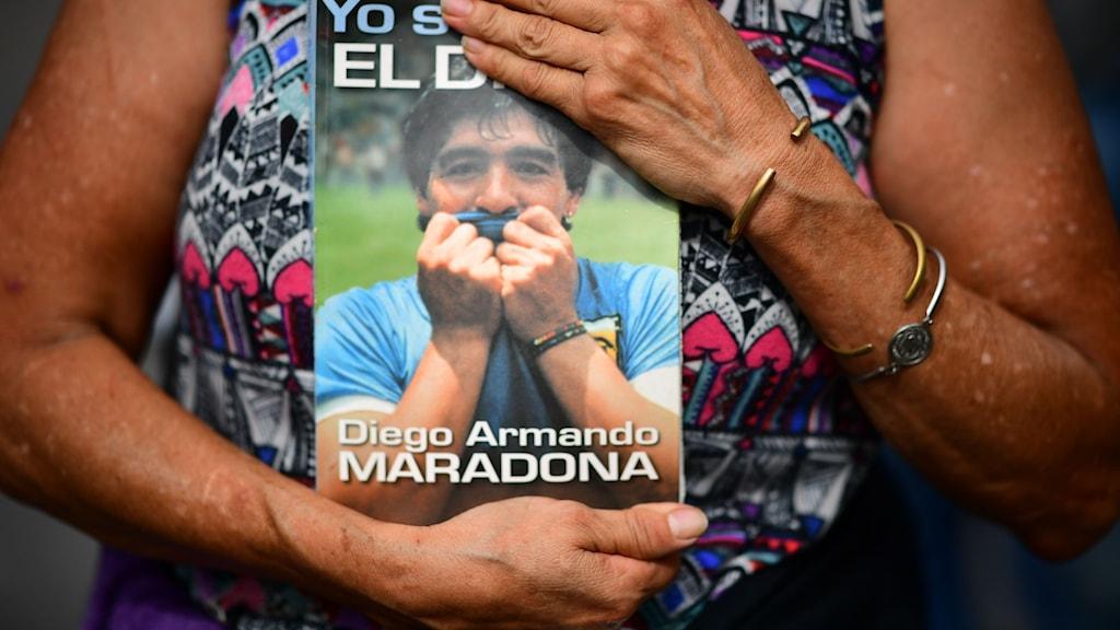 Kvinna håller tidning med Maradona på framsidan, mot bröstet.