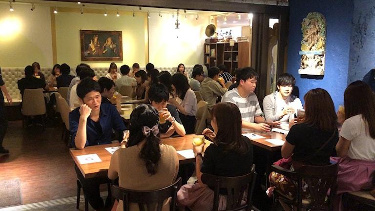Ett 30-tal unga japaner sitter runt bord på speed-dejting.