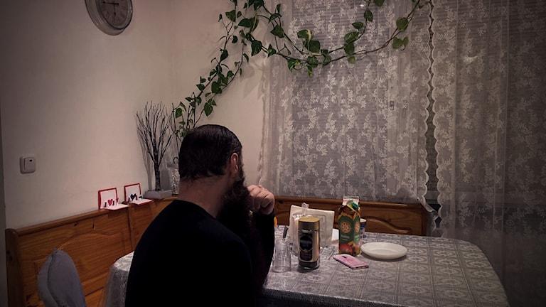 En man sitter med ryggtavlan mot oss vid ett köksbord. Klockan hänger på väggen till vänster och växter slingrar sig längs en annan väg. Gardinerna är fördragna och det står fika framdukat på bordet.