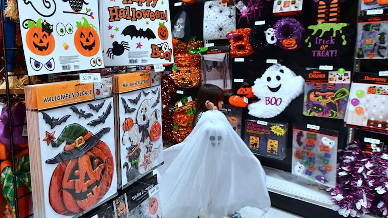 Ett barn går med en spökdräkt i en butik.