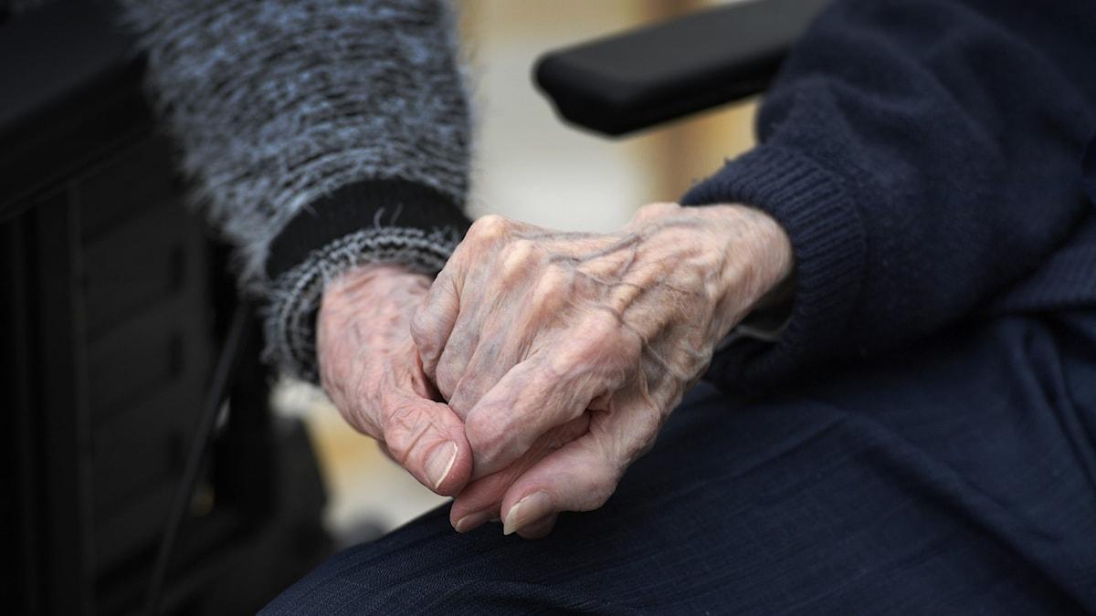 Närbild på två händer som håller i varandra. Händerna är knotiga, rynkiga och ådriga