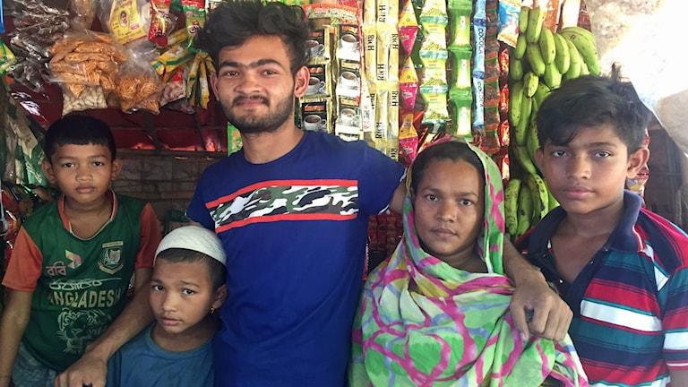 Belal och hans familj framför den nya butiken.