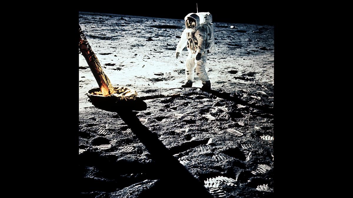 Bilden visar rymdfarkosten stående på månen. En av besättningsmännen går på månen. Fotspår på månytan.