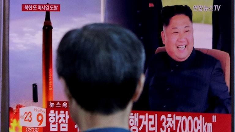 En man tittar på en tv som visar en skrattande Kim Jong-Un jämte en robot.