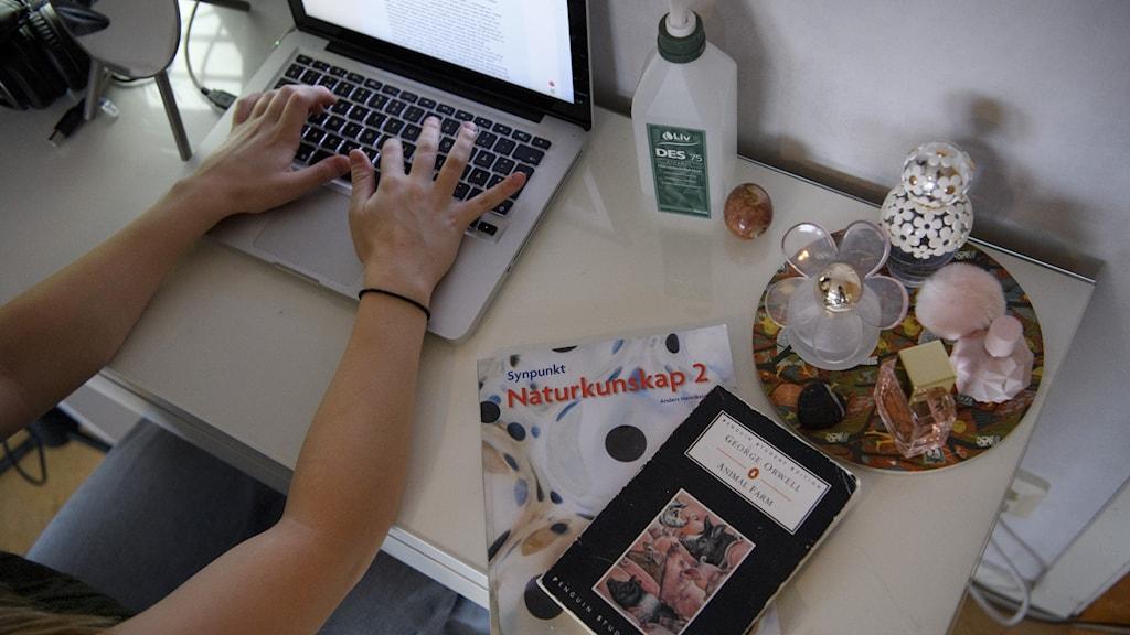 Bild på en gymnasielev som sitter hemma vid en dator och studerar.