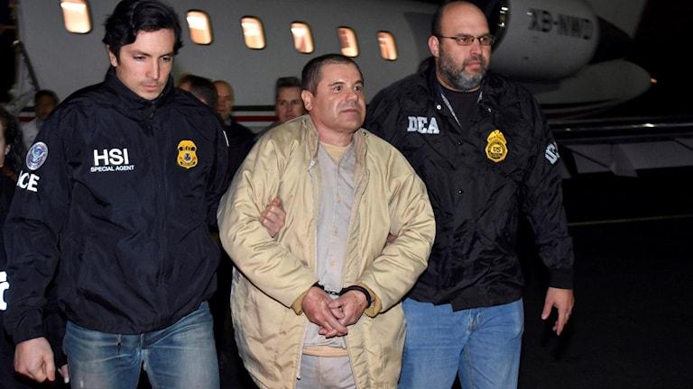 """Joaquin """"El Chapo"""" Guzman eskorteras av två polismän."""