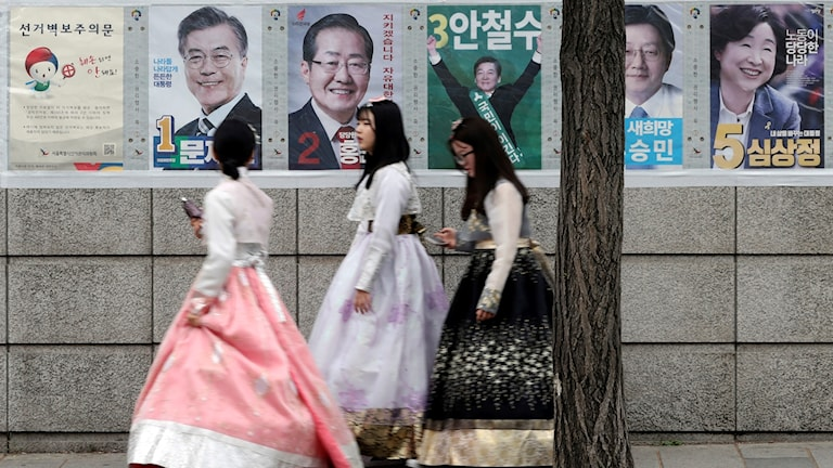 Kvinnor går förbi valaffischer på en gata