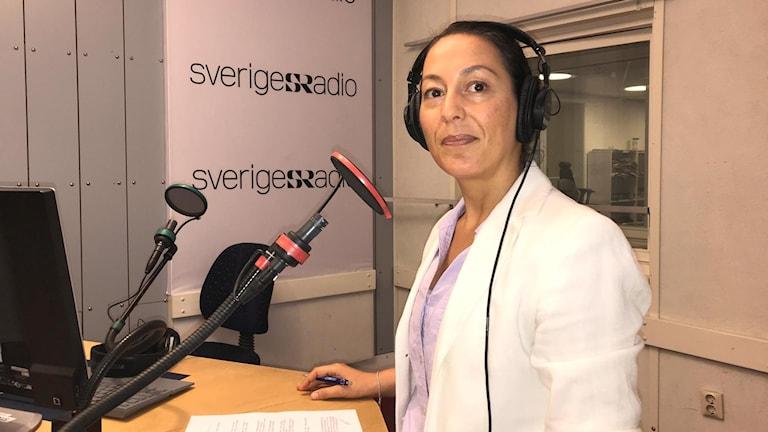 kvinna i sr radiostudio, klädd i vitt, tittar rakt in i kameran