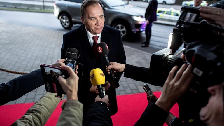 En man står på en röd matta med mikrofoner framför sig.