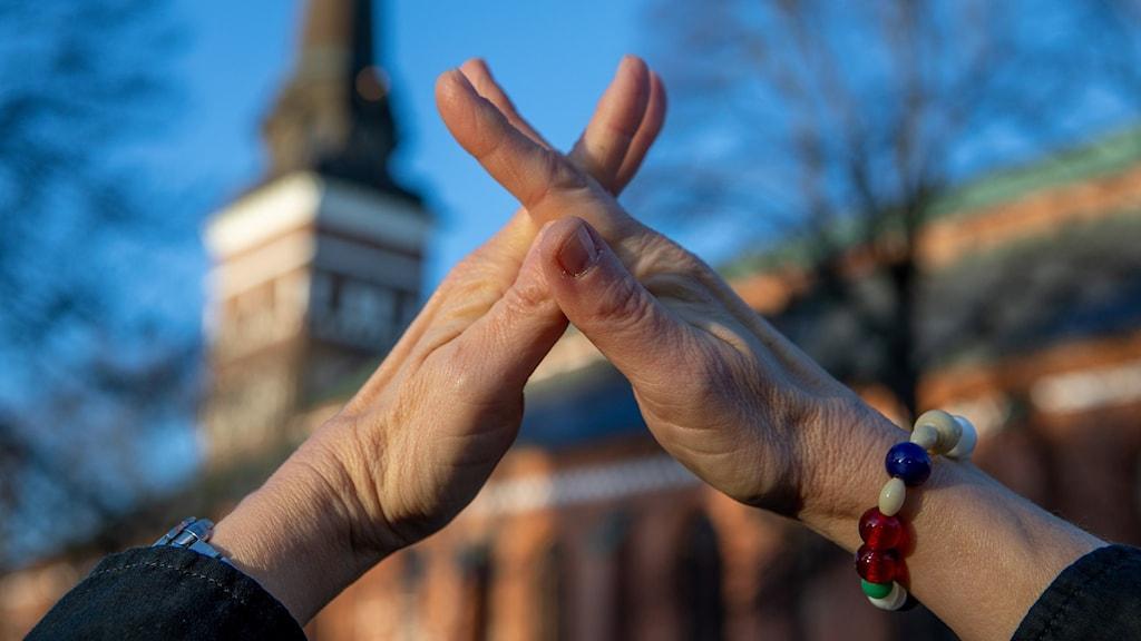 En präst håller upp sina händer med fingrarna  i kors mot ett kyrktorn.