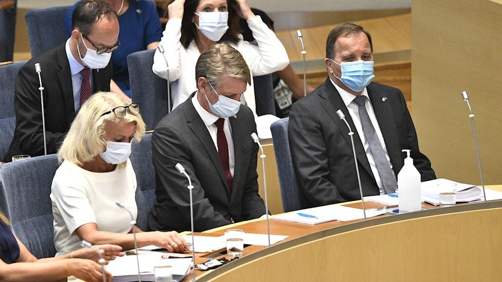 En bild på statsminister Stefan Löfven och några av regeringens ministrar, i riksdagen. De har munskydd  på sig.