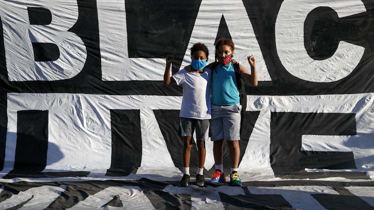 Två personer fram för ett stort tygstycke med texten Black Lives Matter, skrivet i svart och vitt.