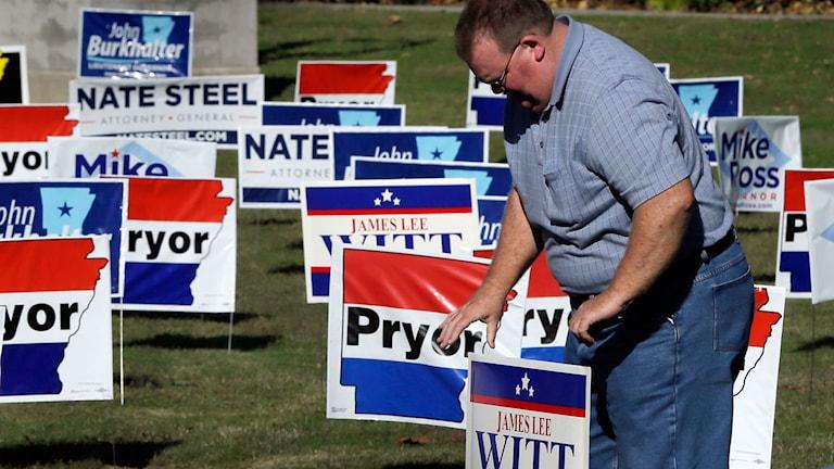En av demokraternas volontär som placerar ut kampanjskyltar på en gräsmatta.
