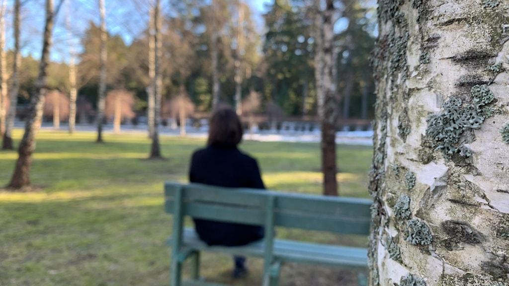 Kvinna sitter vänd mot kameran på en bänk.