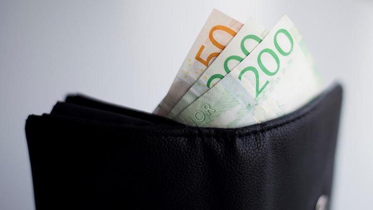 Svart plånbok med två 220-kronorssedlar och en 50-kronorssedel som sticker ut.