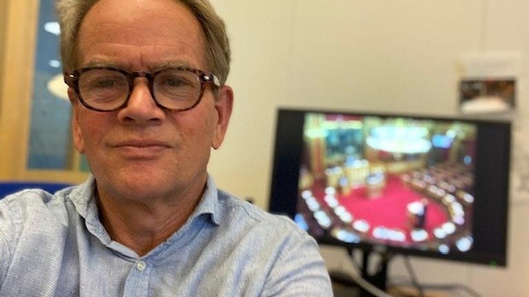 Man i glasögon och ljusblå skjorta tittar in i kameran