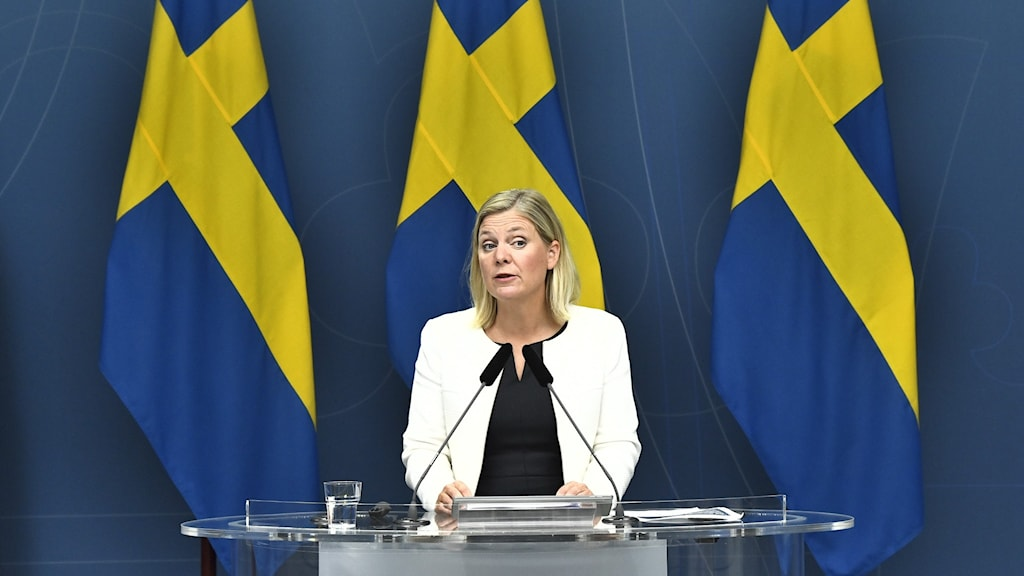 Finansminister Magdalena Andersson framför tre svenska flaggor.