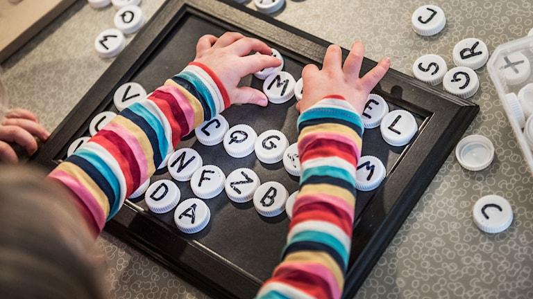 barn som leker med bokstavsknappar