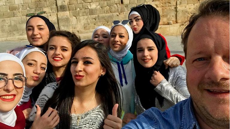 På ett torg i Aleppo spelar ett gäng unga kvinnor fotboll. De saknar männen säger dem.
