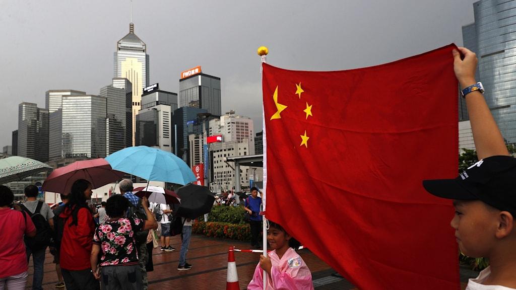 En kinesisk flagga hålls uppe framför Hongkongs skyline