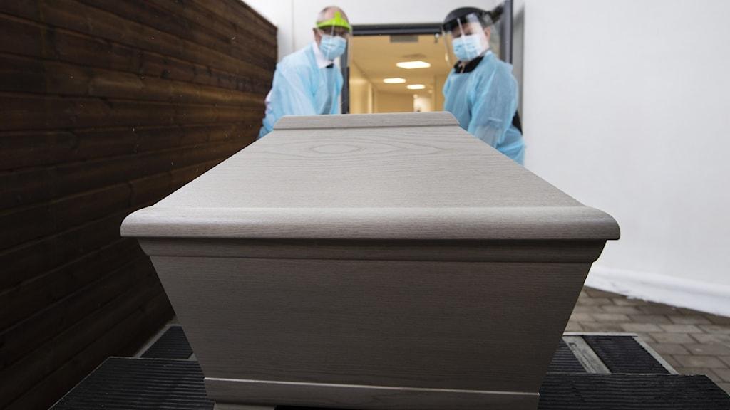 Kista i bårhus, personal med skyddsutrustning, personen avliden i Covid-19.